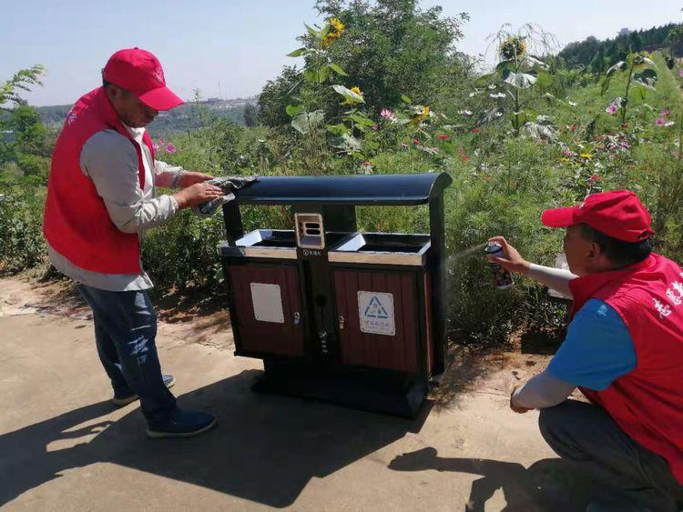 红石林景区志愿者对景区垃圾设施进行清理维护
